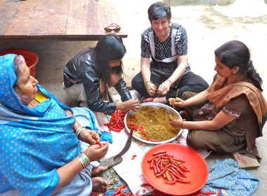 Susan Wallace and village women stuffing spices into red chilies (February 2010)
