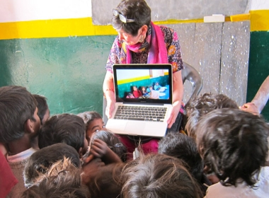 Susan Wallace with laptop and village children
